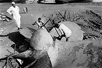 India. Province of Gujarat. Alang. Workers, all men, are sawing a propeller blade by hand. Their boss, dressed in white cotton clothes. looks at the work. Ships aground. Vessels stranded. Bottoms of ships at low tide on the shore. Alang, located in the Gulf of Khambhat, is a ships breaking place. Alang is considered as the biggest scrapyard in the world. Ships recycling for its metals. Environmental issues. Hazardous waste. © 1992 Didier Ruef