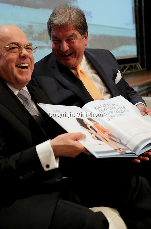 Foto: VidiPhoto..ARNHEM - Persconferentie van het Duitse energiebedrijf RWE en het Nederlandse Essent die de overname van Essent bekend maken. Foto: Michiel Boersma (l) en Jürgen Grossman met een boek over de voordelen van de samenwerking.