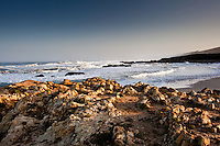 The rocks glow in the early morning light at Pescadero State Beach, California.