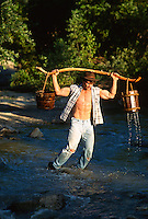 Man carrying a water hauling device over his muscular shoulders
