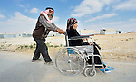 A man pushes his wife in a wheel chair in the Zaatari refugee camp near Mafraq, Jordan. Established in 2012 as Syrian refugees poured across the border, the camp held more than 80,000 refugees by 2015, and was rapidly evolving into a permanent settlement. The ACT Alliance provides a variety of services to refugees living in the camp.