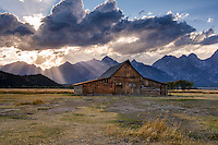 Wyoming Afternoon. While driving to my camp site in the dull light of late afternoon, I noticed sun rays developing behind the Moulton Barn and had to stop for a photo. As quickly as these beams of soft light emerged, the clouds drifted and the rays were gone.  It was a brief and lovely moment in a timeless western scene. Teton National Park, Wyoming.