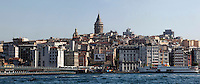 Panoramic view of Galata Bridge, 1994, and Galata Tower, (Galata Kulesi), Istanbul, Turkey, in the morning. The Galata bridge, the fifth between Karakoy and Eminonu,, was built by STFA and designed and supervised by GAMB. It is a 490 m long bascule bridge, with a main span of 80 m, and a 42 m wide deck and has 3 traffic lanes and one walkway in each direction plus tram tracks connecting suburban  Zeytinburnu to Kabatas. Picture by Manuel Cohen.