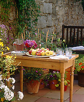 Terracotta pots containing sweet peas, geraniums and hydrangeas surround a garden table laid with a jug and glasses