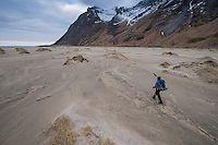 Female hiker hiking across sand at Horseid beach, Moskenesøy, Lofoten Islands, Norway