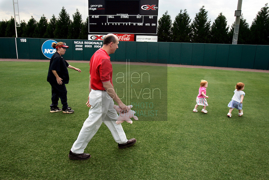 UGA softball coach Lu Harris-Champer (left) and her husband, assistant swimming coach Jerry Champer, play in the softball stadium with their twin daughters, Emma (in white shirt) and Jenna, on Wednesday, May 17, 2006. Harris-Champer is due to give birth to another daughter early next week.