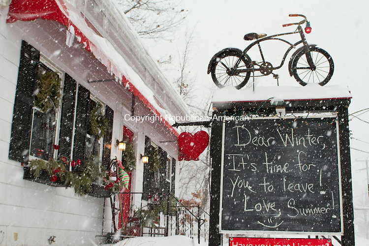 WATERTOWN, CT 13 February 2014-021314LW03 - A sign in front of the Plaid Poppy gift shop on Main Street in Watertown longs after summer as snow flies Thursday afternoon.<br />