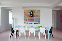 A colourful psychedelic artwork is the focus of the dining area which is furnished with a geometric-patterned table