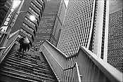 A worler climbs the stairs leading to the skyscraper business district of Nishi-Shinjuku, Tokyo, Japan.