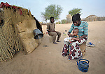 A woman feeds her child outside the family's home in Timbuktu, a city in northern Mali which was seized by Islamist fighters in 2012 and then liberated by French and Malian soldiers in early 2013. This family belongs to the Bella ethnic group, which has traditionally been exploited by Timbuktu's lighter-skinned groups.