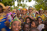 Young women and children in the small, rural village of Bele Kwara in southwestern Niger run towards the camera for what may be the first picture of their lives.