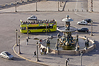 Open-air tour bus with tourists passes fountain in Place de la Concorde, Central Paris, France