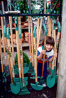 Little boy smiling looking into camera making eye contact at garden center with display of children's gardening tools