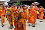 Bhuddist novices and monks during a funeral procession for a deceased Abbott with residents showing their respect in Luang Prabang, Laos.