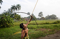 Viriunaveteri, Venezuela. Yanomami hunter showing his skill...The village of Viriunaveteri consists of 15 huts around a muddy square. It's situated in the Venezuelan Amazone several days by boat from the nearest town. This community on the banks of the Casiquiare is one of the few Yanomami villages that actually has some contact with the outside world. Most other tribes live deeper in the jungle.
