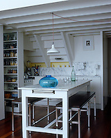 A small kitchen in a Parisian apartment with floor-to-ceiling shelving to maximize the space.