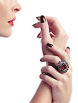 Woman hands with fancy nail polish and a red stone ring close to her lips isolated on white background