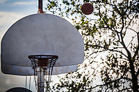 A basketball arcs while making its way to the basket, maybe.