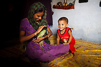 Sadma Khan, 19, plays with Lucky, a pet parakeet, in her mother's one-room house which she shares with 5 other family members in a slum area of Tonk, Rajasthan, India, on 19th June 2012. She was married at 17 years old to Waseem Khan, also underaged at the time of their wedding. The couple have an 18 month old baby (in red) and Sadma is now 3 months pregnant with her 2nd child and plans to use contraceptives after this pregnancy. She lives with her mother since Waseem works in another district and she can't take care of her children on her own. Photo by Suzanne Lee for Save The Children UK
