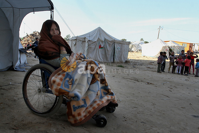 A Palestinian woman sits outside her tent donated by a charity organisation as temporary housing for those whose houses were destroyed during a seven-week Israeli offensive, in Khuzaa, east of Khan Younis, in the southern Gaza Strip, on March 01, 2015. Photo by Abed Rahim Khatib
