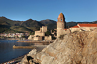 Eglise Notre Dame des Anges, Collioure, France, with Chateau Royal in the distance and rocks in the foreground. The bell tower was converted from a medieval lighthouse and the Mediterranean Gothic style nave was built in 1684. The dome was added to the bell tower in 1810. Picasso, Matisse, Derain, Dufy, Chagall, Marquet, and many others immortalized the small Catalan harbour in their works. Picture by Manuel Cohen.