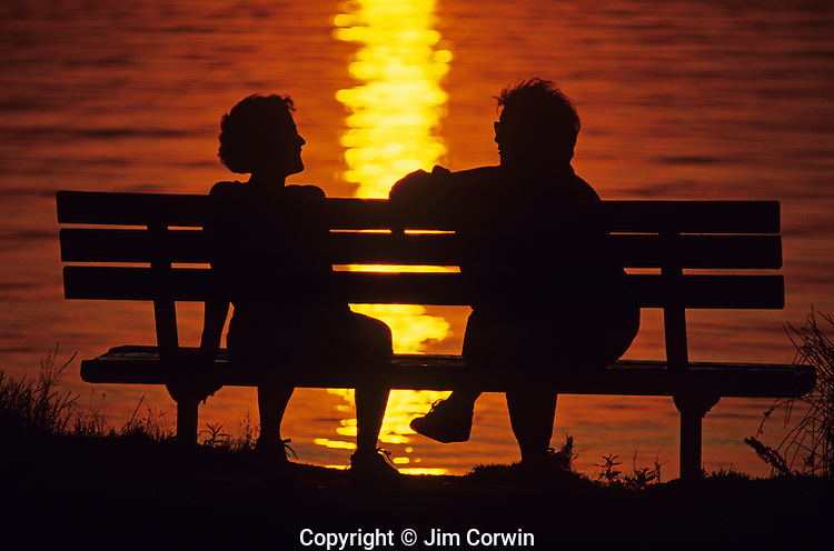 Sunset at Greenlake with silhouetted couple on park bench sitting and talking while enjoying the beautiful sunset Seattle Washington State USA