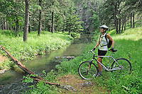 Bicycle rider crossing river, Grace Coolidge Walk-in Fishing Trail, Custer State Park, Black Hills, South Dakota, USA