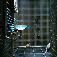 The walls of this wet room are covered in grey ceramic tiles while the floor tiles are of functional slate
