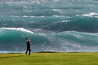During a lull in a massive winter storm with seas to six and a half meters and torrential rain with wind gusts to over 100 knots a lone golfer negotiates a very Serious Water Trap with a wave that appears to be breaking over his head at Sea View Golf Club Cottesloe