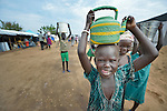 A girl carries water from a communal water point inside a camp for internally displaced families located inside a United Nations base in Juba, South Sudan. The crowded camp holds Nuer families who took refuge there in December 2013 after a political dispute within the country's ruling party quickly fractured the young nation along ethnic and tribal lines. More than 20,000 people are living in the camp.