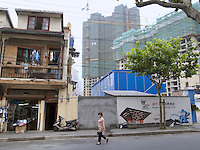 China. Shanghai. Downtown. Town center. A woman walks on the concrete road and passes near old traditional house ( which will be destroyed in the future) and new modern building under construction. Billboard of  the Expo 2010 Shanghai China  on the wall.. World Expo. Drawing on the China Pavilion. 26.06.10 &copy; 2010 Didier Ruef
