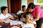 Central America, Costa Rica, Puerto Jiminez. Teacher helps child at Esculea Carbonera, a small school nearby Lapa Rios.