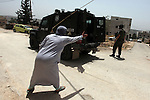 A Palestinian woman shouts at an Israeli border guard during clashes following a protest against the expropriation of Palestinian land by Israel on March 31, 2013 in the village of Kfar Qaddum, near the occupied West Bank city of Nablus. Photo by Issam Rimawi