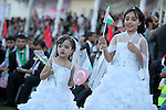 Palestinian girls wave Turkish flags during in a mass wedding ceremony in Gaza City, on May 31, 2015. Nearly 2000 Palestinian couples were married in a ceremony funded by the Turkish government and supported by the Hamas movement. Photo by Ashraf Amra