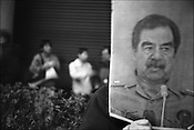Outside the American embassy in Tokyo, during an anti-American and anti-Iraq war demonstration, a Japanese person holds a portrait of Iraqi dictator Sadam Hussein. Tokyo, Japan.