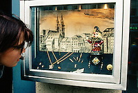 Switzerland. Basel. Fasnacht Carnival. A woman looks at the golden necklaces and wrings exposed in a shop window of a jeweller's shop. A small figure is laid near a drawing of the old town. © 1997 Didier Ruef