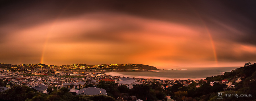 This image which was shot overlooking Lyall Bay in Wellington, New Zealand on the 28th May 2013. It is a 90 second exposure during which this amazing light from a setting sun behind me lit up the clouds and landscape. To add to this, a huge rainbow appeared right on cue! All of this after a bitterly cold day which brought hail, sleet and snow and a gale force southerly wind to the Wellington region.