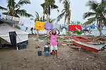 A woman hangs laundry to dry on Jinamoc Island, part of the municipality of Basey in the Philippines province of Samar that was hit hard by Typhoon Haiyan in November 2013. The storm was known locally as Yolanda. The ACT Alliance has been providing a variety of assistance to survivors here, and is planning a long-term rehabilitation program with residents.