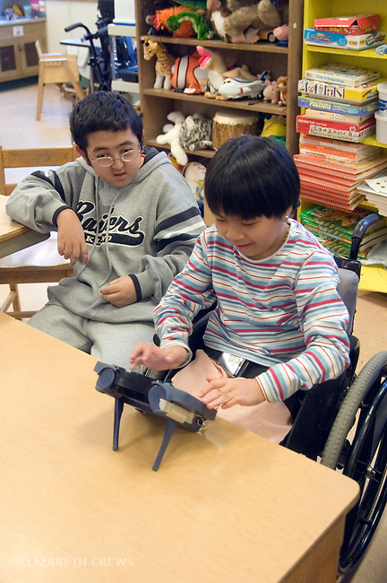 Oakland CA Developmentally disabled primary school students working with AAC (Alternative augmentative communication) devices in special education classroom  MR