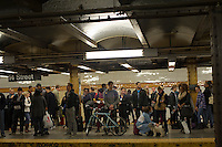 Transit riders are seen waiting for an uptown subway train at the West 14th Street subway station on the Eighth Avenue subway line before the shutdown of the transit system because of Hurricane Sandy, in New York on Sunday, October 28, 2012.  A MTA announcement said trains were delayed due to a police investigation. Due to Hurricane Sandy, New York shut down the subways at 7 PM on Sunday.  (© Frances M. Roberts)