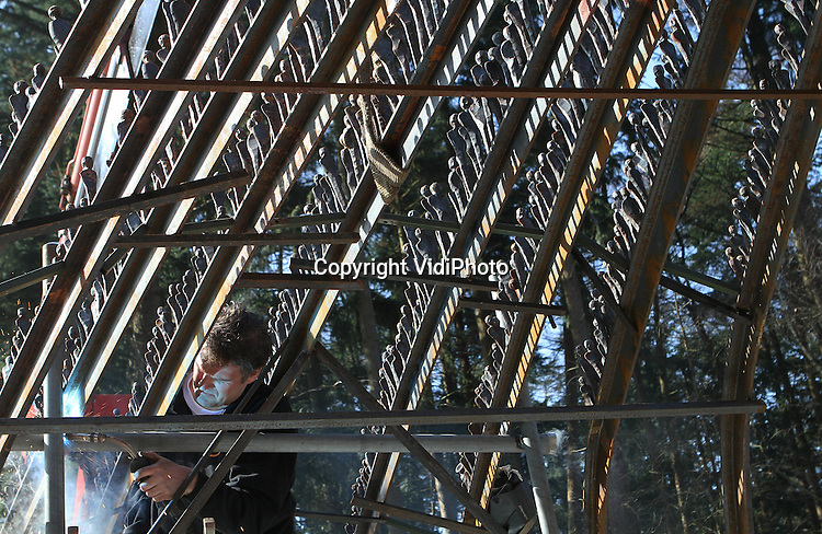 Foto: VidiPhoto..ARNHEM - Zeven Nederlandse smeden hebben donderdag gezamenlijk hun kunstwerk geplaatst voor het Nederland Openlucht Museum in Arnhem. Het betreft een cadeau van dit zogenoemde Smeedcollectief aan het museum, dat dit jaar een eeuw oud is. Het enorme metalen kunstwerk, waar enkele tonnen staal in verwerkt zijn, staat voor de entree van het museum. Het kunstwerk bestaat uit honderden metalen poppetjes (de bezoekers van het museum) die over een soort loopbrug dezelfde richting uitlopen..