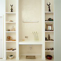 Objects Bonnie Young has collected on her travels are displayed on the shelves surrounding the wash basin in the master bedroom