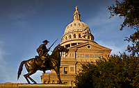 Bronze Texas Ranger statue monument stands in front of the Texas State Capitol Dome on a bright sunny day with blue skies.