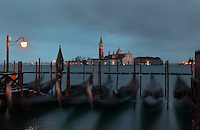 The Church of San Giorgio Maggiore, a 16th century Benedictine church designed by Andrea Palladio in Renaissance style and built 1566-1610, on the island of San Giorgio Maggiore, seen from St Mark's Square or the Piazza San Marco, past moored gondolas. The city of Venice is an archipelago of 117 small islands separated by canals and linked by bridges, in the Venetian Lagoon. The historical centre of Venice is listed as a UNESCO World Heritage Site. Picture by Manuel Cohen