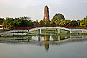 TH00327-00...THAILAND - Bridge over a canal in the Phra Ram Park located at the center of the Ayutthaya Historical Park and the chedi at Wat Phra Ram.