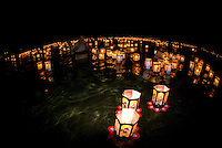 A man photographs paper lanterns at the annual bon dance and Toro Nagashi (ìfloating lanterns set out to seaî) ceremony in Haleiwa. Inscribed with the names of the departed, the lanterns ride the outgoing tide to greet visiting spirits.