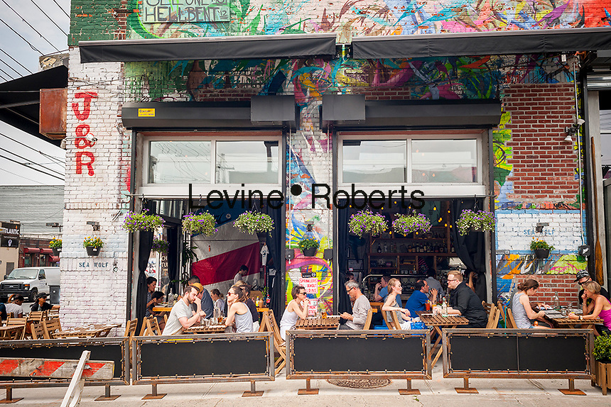 "Al fresco dining in Bushwick, Brooklyn in New York during the annual Bushwick Collective Block Party on Saturday, June 4, 2016. Music and partying brought some but the real attraction was the new murals  by ""graffiti"" artists that decorate the walls of the buildings that the collective uses.  (© Richard B. Levine)"