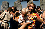 1970's style hippies attend the second free festival at Stonehenge to celebrate the summer solstice June 21st 1975. Baptism of hippy children.