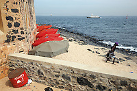 Senegal. Goree island. IFAN historical museum is located in an old fortress. The history of slave trade, of french colonialism and the recent senegale history is on display in the various sections of the museum. An african tourist is walking on the sandy beach at the bottom of IFAN museum. A red upside-down dustbin full of garbage with the words written: I love Goree. A boat is cruising on the Atlantic ocean. 06.12.09 © 2009 Didier Ruef / The Global Fund