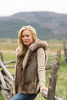 blonde woman wearing a fur vest while leaning on a wooden fence in Taos, NM